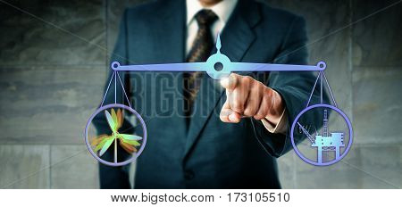 Corporate manager equilibrating a vibrant wind power symbol and an offshore oil and gas platform on a virtual weighing scale. Industry and business concept for energy turn efficiency and resources.