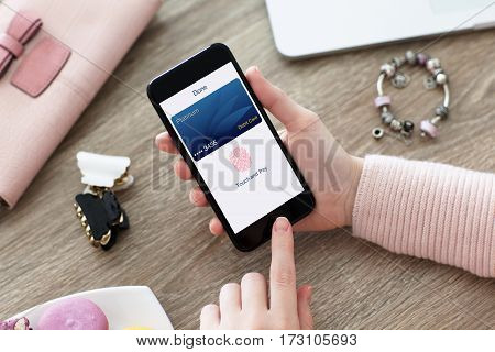 female hand holding phone with debit card app touch pay on screen
