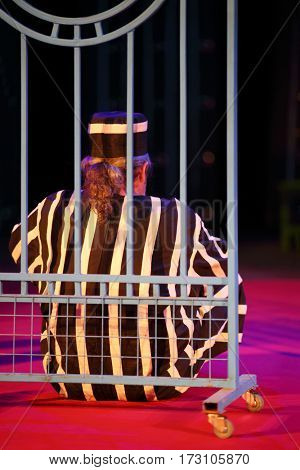 MOSCOW - OCT 19, 2016: Back of actor prisoner behind lattice during Premium class Performance in Modern theater