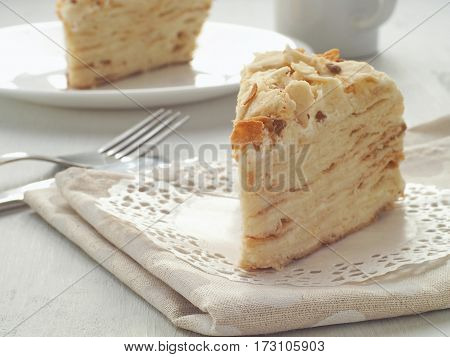 Piece of multi layered cake close-up. Mille feuille dessert. Crumbs decorated torte on white doily upon wooden table. Food background, blur. Selective focus on the front.