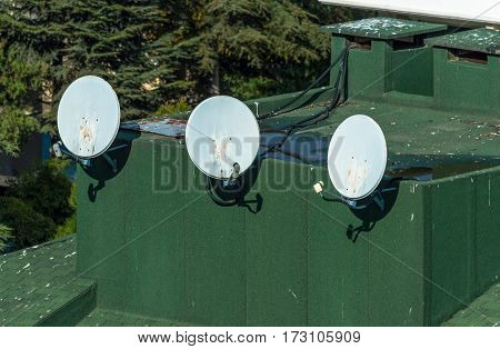 Satellite dishes satellite antennas mounted on the green roof of a building
