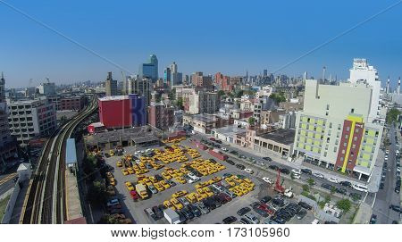 NEW-YORK - AUG 25, 2014: Cityscape with car parking near railway and Home2 Suites by Hilton at summer sunny day. Aerial view