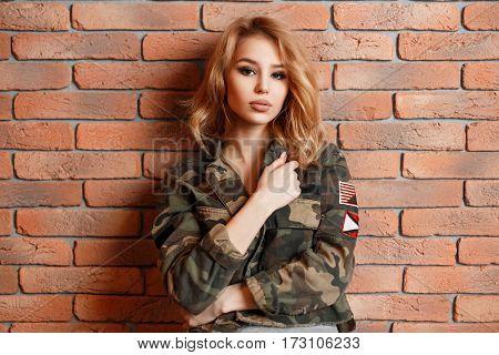 Young Beautiful Woman In Stylish Fashion Jacket Near A Brick Wall