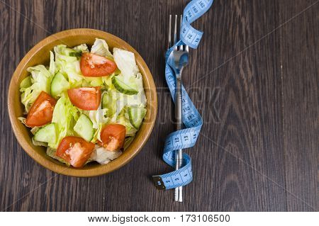 Salad In Wooden Bow,forkl And Measuring Tape On A Table Close-up.