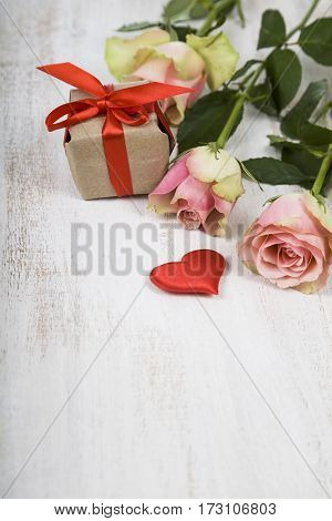 Pink roses gift and hearts on a wooden background. Greeting card with Valentine's Day Birthday or Wedding.
