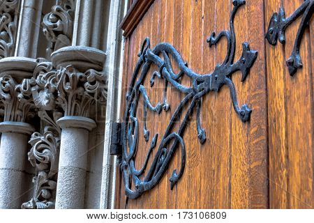Close up of ornate metalwork on a church door and ornate carvings.