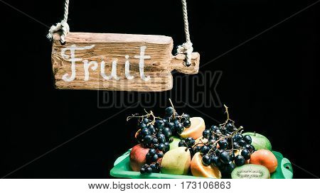 Retro wooden sign hanging above the counter with various fruit. Isolated over black background