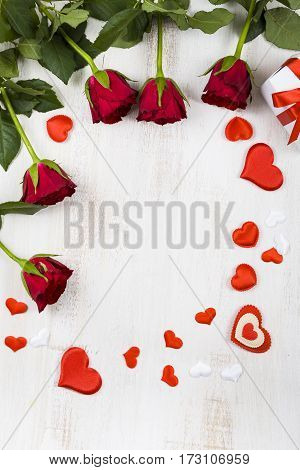 Frame Of Red Roses And Hearts On A Wooden Background.