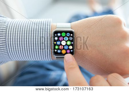 Man hands and smart touch watch with home screen icons apps