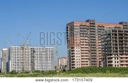 A number of high-rise buildings under construction in white and brown.