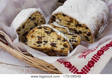 German Christmas stollen cut into slices powdered in wicker basket kitchen towel with ornament top view close up