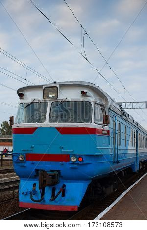 Train in blue standing at the station