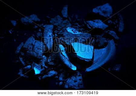 Crushed eye shadow isolated on black background vith spooth light. Beauty and fassion style.Eye shadow of blue color.