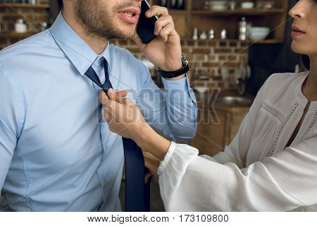 partial view of businesswoman tying husband's tie