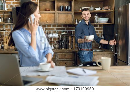 Happy young woman with smartphone and coffee cup looking at man with bowl