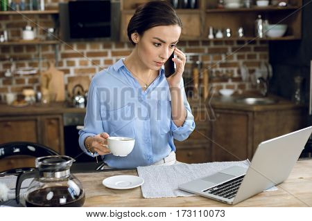 Young businesswoman with coffee cup using laptop and talking on smartphone