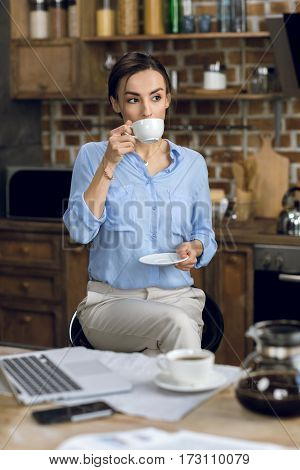 Attractive young businesswoman drinking coffee at morning
