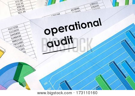 Paper with title operational audit and financial data on a table.