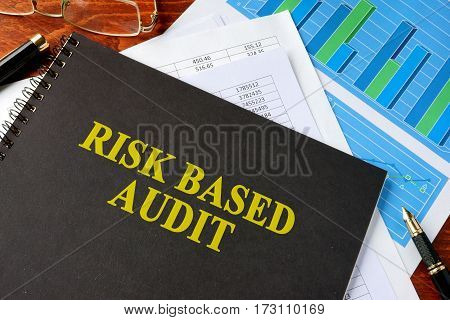 Book with title risk based audit on a table.