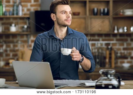 Pensive young man with coffee cup standing at table with laptop