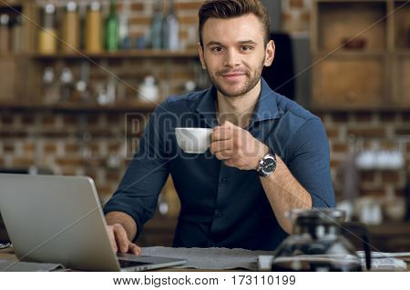 Handsome young man with coffee cup using laptop and smiling at camera