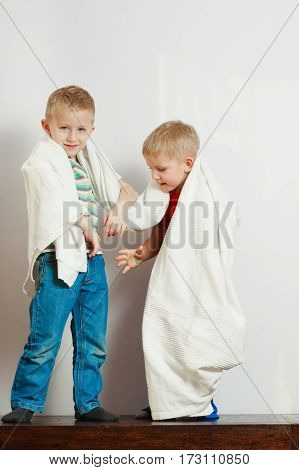Childhood relationship between brothers concept. Two little boys siblings playing together with towels and having fun.