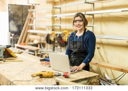 Woman Working In A Woodshop With Laptop
