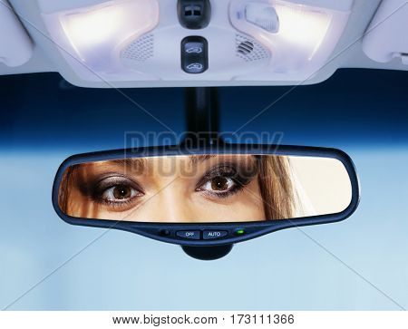 Young woman sits on driver's seat and Looks in the rear-view mirror