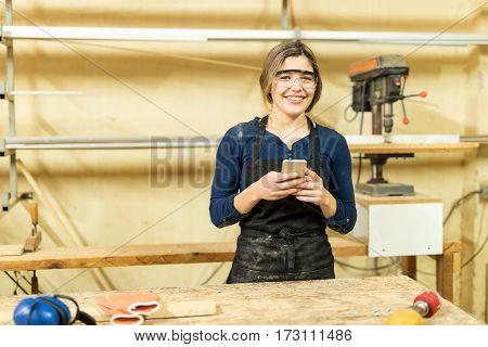 Cute Hispanic Carpenter Using Smartphone