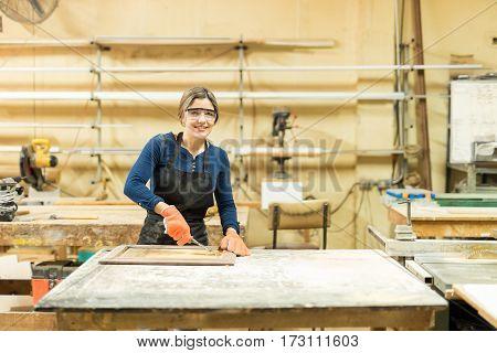 Pretty Carpenter Using A Wood Gouge