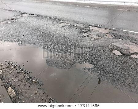 Damaged asphalt road with potholes. Spring background
