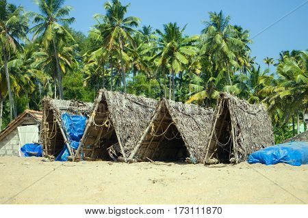 Fishing huts for fishing nets and relaxing. On shore of Bay of Bengal. Kerala