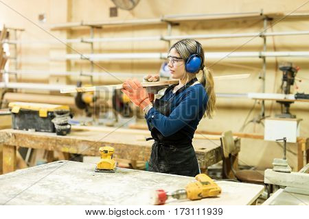 Woman Carrying A Wood Board At Work