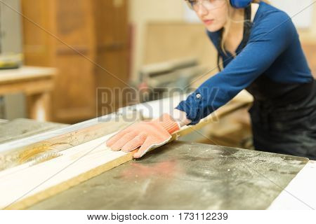 Female Carpenter Cutting Wood With A Saw