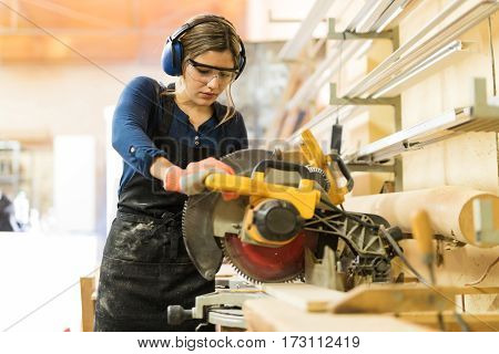 Woman Using Power Tools In A Woodshop