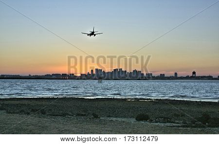 A airliner see from behind as it lands into the setting sun at Boston International Airport. The sun is seen just behind the skyline of Boston.