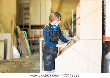 Woman Hammering Some Nails At Work