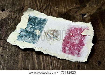 the flag of Mexico in an aged piece of paper on a rustic wooden background