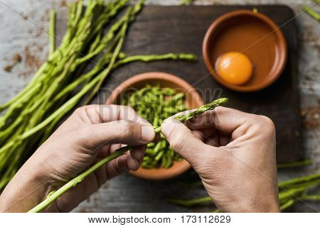 young man chopping wild asparagus with his hands and some earthenware bowls with chopped asparagus and a cracked egg, the ingredients to prepare an asparagus omelet, on a rustic wooden surface