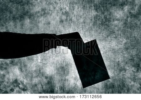 the shadow of a man man with an envelope in his hand behind a gray fabric, as he was voting