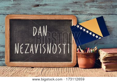 a chalkboard with the text Dan Nezavisnosti, Independence Day written in Bosnian, a pot with pencils, some books and the flag of Bosnia and Herzegovina, on a wooden desk