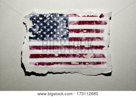 the flag of the United States in an aged piece of paper on an off-white background
