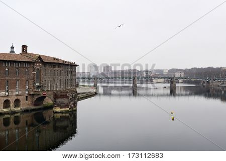 a view o the Garonne River as it passes through Toulouse, France, in a foggy day with the bridge Pont Saint Pierre in the background and the Hotel-Dieu Saint-Jacques on the left