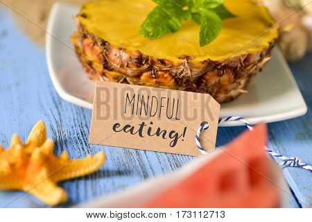 a brown paper label with the text mindful eating in front of some slices of pineapple and a piece of watermelon on a blue rustic wooden table