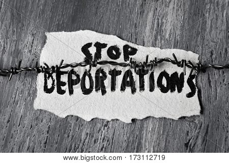 closeup of a barbed wire and a piece of paper with the text stop deportations handwritten in it on a rustic wooden surface