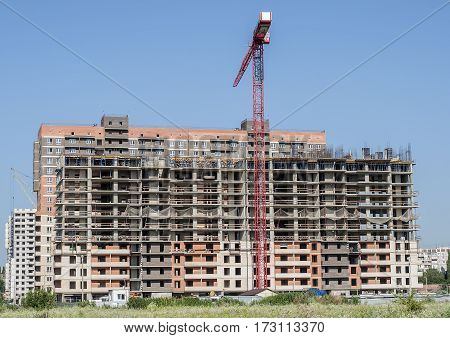 Construction crane on a background of a new high-rise building close-up.