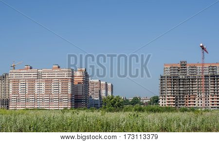 Panorama of under construction residential district in the territory of green grass.