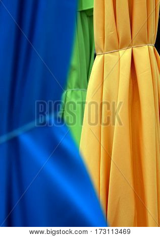 A colorful outdoor umbrella abstract with blue, yellow, and green layers of bunched materials