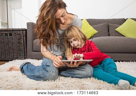 Child Touching Tablet With Mother At Home