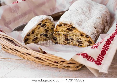 Homemade Christmas stollen with cut off slice with knife in wicker basket kitchen towel parchment paper top view